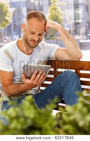 Young man sitting outdoors on a bench, using tablet computer, using headphones.