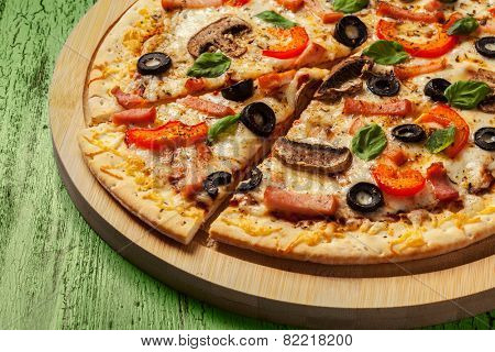 Ham pizza with capsicum, mushrooms, olives and basil leaves on wooden board on painted green table close up