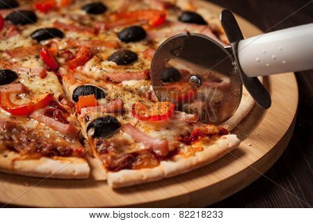 Pizza cutter (wheel) slicing ham pizza with capsicum and olives on wooden board on table