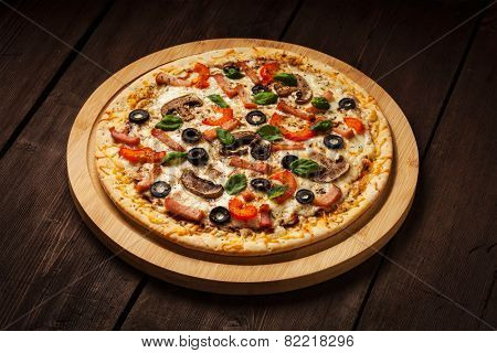 Ham pizza with capsicum, mushrooms, olives and basil leaves on wooden board on old table