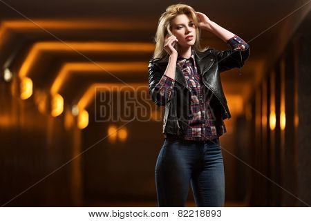 Young fashion blond woman in leather jacket calling on mobile phone