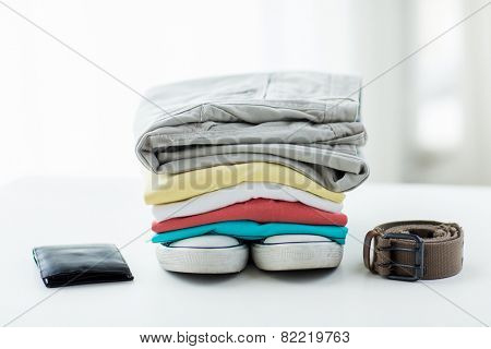 clothes and personal staff concept - close up of folded shirts, pants, belt, wallet and shoes on table at home