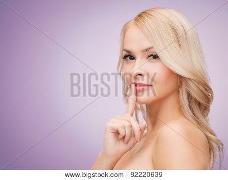 health, people and beauty concept - beautiful young woman holding finger on her lips over violet background