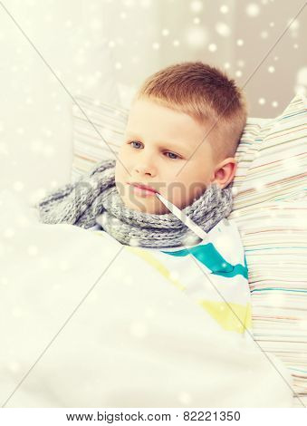 childhood, healthcare and medicine concept - ill boy with thermometer lying in bed and measuring temperature at home