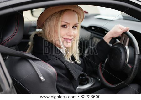 Attractive blond woman in a trendy hat at the wheel of her car turning to smile at the came ram view through the side window