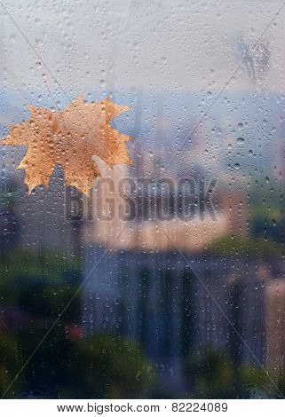 Autumn, rainy city through a window with raindrops. autumnal mood.