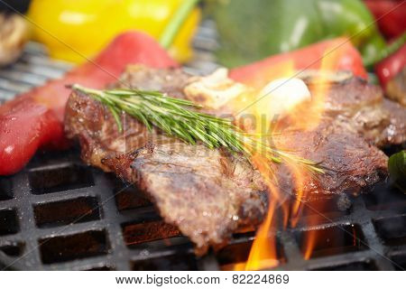 T-bone steak on the barbecue grill with vegetable spears in the background