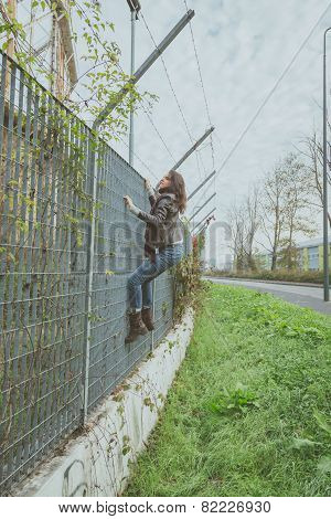 Beautiful Young Brunette Climbing Over A Fence