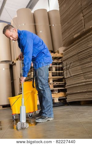 Portrait of focused man moping warehouse floor