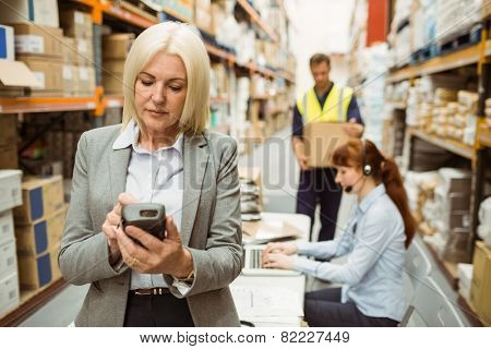 Focused warehouse manager using handheld in a large warehouse