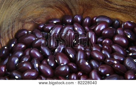 Uncoocked red beans in a olive wood bowl. Gernika beans.