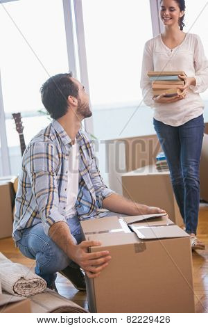 Smiling couple unpacking cardboard boxes in their new home