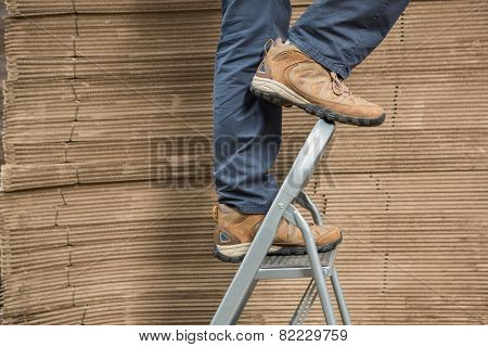 Low section of worker on ladder in the warehouse