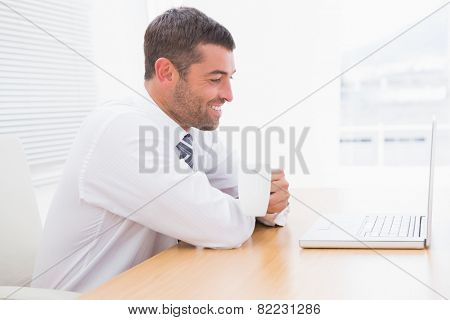 A businessman holding mug at desk in his office