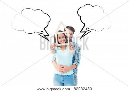 Happy young couple with house shape against speech bubble