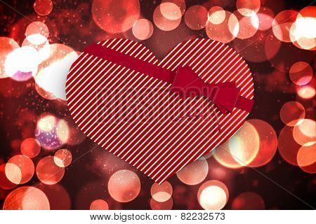 Heart shaped box of candy against twinkling red and orange lights