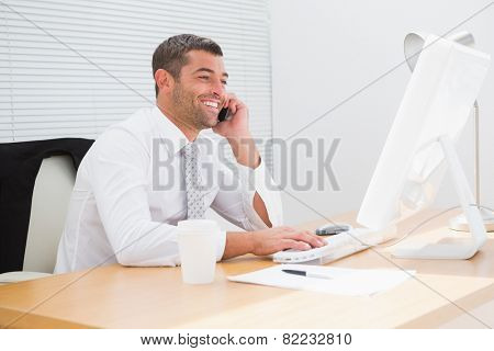 Smiling businessman phoning at his desk in his office