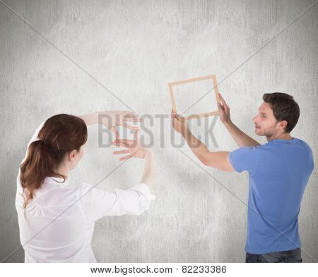 Couple deciding to hang picture against weathered surface