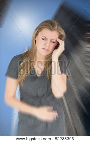 Woman with stomach ache against low angle view of skyscrapers