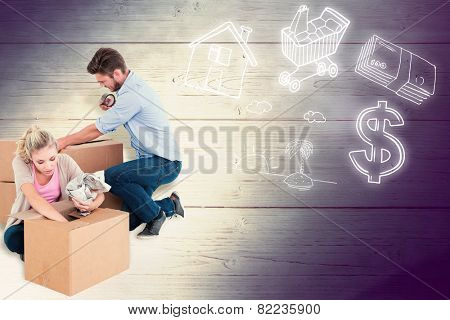 Young couple packing moving boxes against shadow on wooden boards