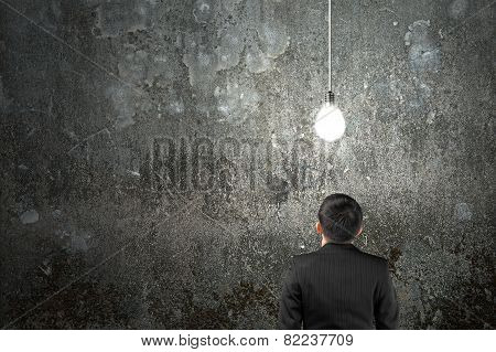 Businessman Looking At Brightly Light Bulb Illuminated Dark Concrete Wall