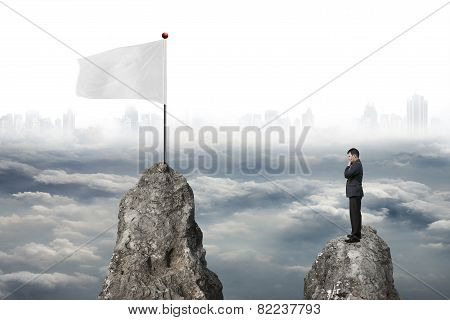 Businessman Standing On Peak With White Flag And Cloudy Cityscape