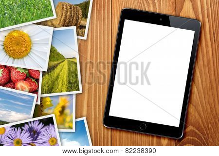 Tablet with blank screen and stack of printed pictures collage on wooden table