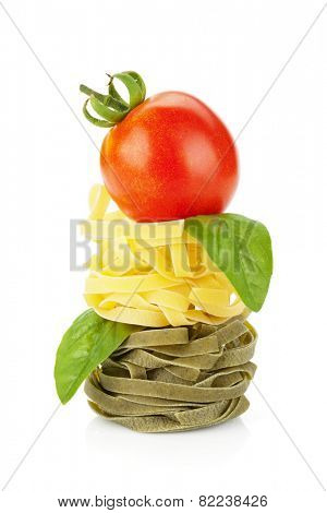 Fettuccine nest pasta with tomato cherry and basil. Isolated on white background