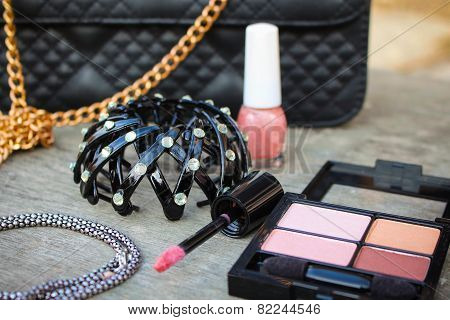 Women's accessories: eyeshadow, lip gloss, nail polish, clip hair, necklace, black handbag