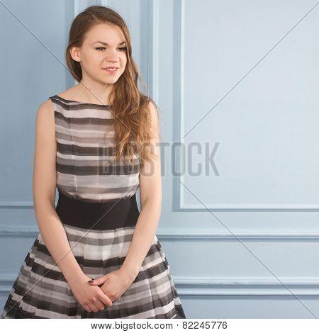Beautiful Girl In A Gray Dress Near Blue Wall