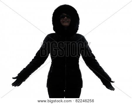 one woman in winter coat arms outstretched happy silhouette on white background