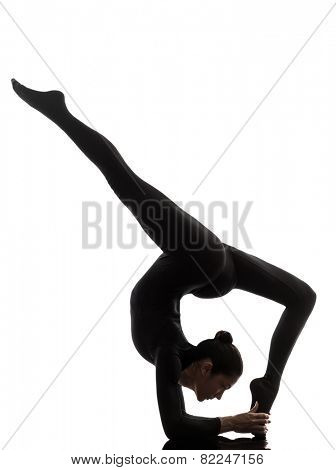 one  woman practicing gymnastic yoga Eka Pada Viparita Dandasana in silhouette on white background