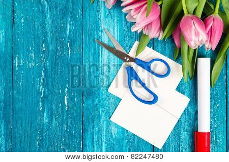 Making a romantic card - tulips and post it notes on wooden table