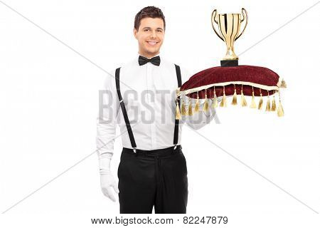 Butler holding a trophy on red pillow isolated on white background