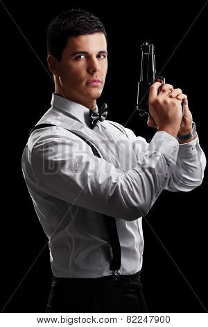 Vertical shot of an elegant man holding a gun on black background