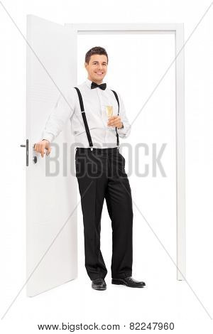 Full length portrait of an elegant guy standing by a door and holding a glass of wine isolated on white background