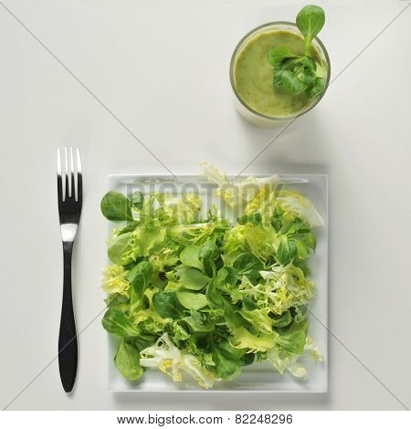 high-angle shot of a plate with a green and a green smoothie on a white table