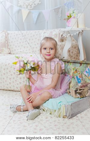 Little girl sitting on small bag with flowers