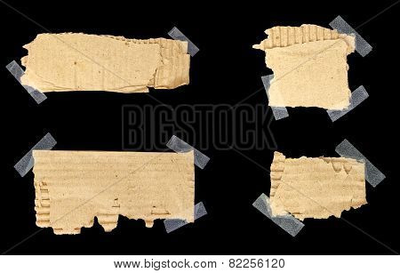 Torn Cardboard Scraps Stuck With Scotch Tape With Copy-space Isolated On Black