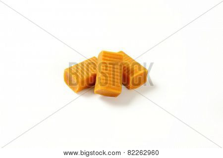 three caramel toffee candies on white background