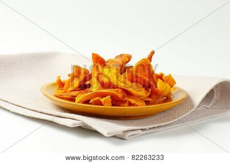 plate of dried mango slices on yellow plate and white place mat