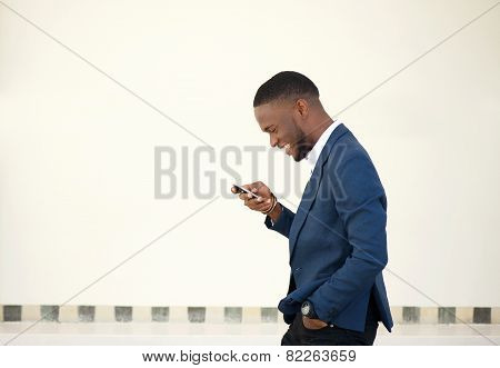 Smiling Businessman Walking And Sending Text Message