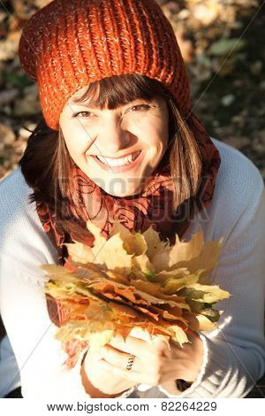 portrait of beautiful woman with autumn orange leaves