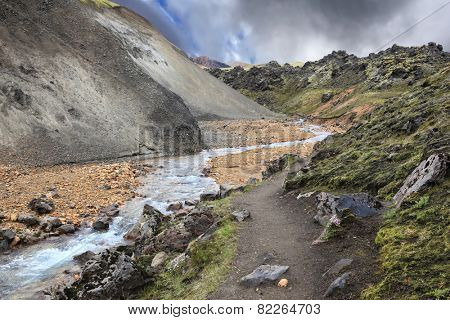 Gorge Valley Landmannalaugar. The path runs along the mossy mountainside. The gorge runs abounding stream