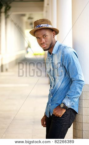 Relaxed Young Man With Hat Leaning On Wall Outdoors