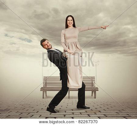happy man holding his woman. smiley young woman in long dress pointing finger at something and looking at camera. photo at outdoor