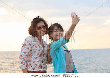 Two Sister Take A Photo,selfie By Smart Phone Beside Sea Beach With Happy Emotion