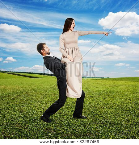 displeased young woman sitting on tired man, pointing at something and screaming. photo at outdoor