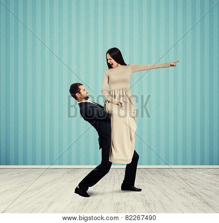 angry screaming woman looking at her man and pointing at something. photo in room with blue wall