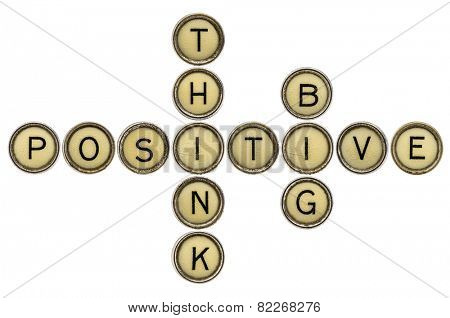 think positive and big crossword  in old round typewriter keys isolated on white